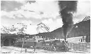 """RGS #20 with southbound Rocky Club railfan excursion at snowshed on Lizard Head section house.  Consist is caboose #0403, coaches #320 & #306 and gondola 1754.<br /> RGS  Lizard Head, CO  Taken by Kindig, Richard H. - 5/30/1947<br /> In book """"RGS Story, The Vol. IV: Over the Bridges? Ophir Loop to Rico"""" page 278"""