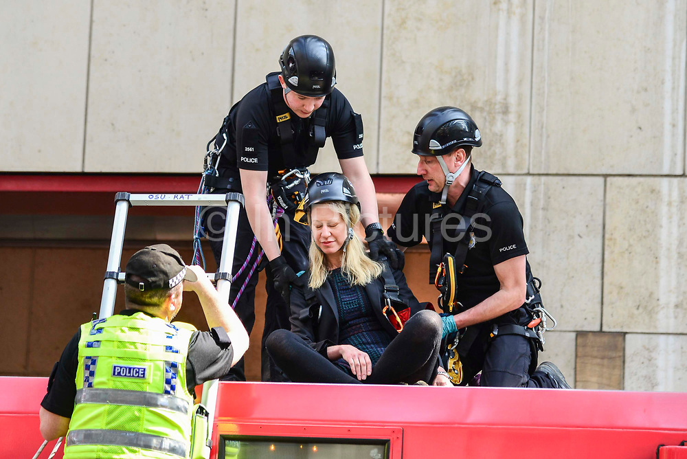 Police officers begin to remove a climate change protesters who glued herself to the roof  of a Docklands Light Railway carriage on April 17, 2019 in London,England, United Kingdom. This is the third day of a coordinated protest by the Extinction Rebellion group who are demanding the government decisive action from the UK Government on climate change.