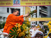 12 OCTOBER 2015 - BANGKOK, THAILAND:  A Mahayana Buddhist monk sprinkles water on people lining Yaowarat Road on the first day of the Vegetarian Festival in Bangkok's Chinatown. The Vegetarian Festival is celebrated throughout Thailand. It is the Thai version of the The Nine Emperor Gods Festival, a nine-day Taoist celebration beginning on the eve of 9th lunar month of the Chinese calendar. During a period of nine days, those who are participating in the festival dress all in white and abstain from eating meat, poultry, seafood, and dairy products. Vendors and proprietors of restaurants indicate that vegetarian food is for sale by putting a yellow flag out with Thai characters for meatless written on it in red.     PHOTO BY JACK KURTZ