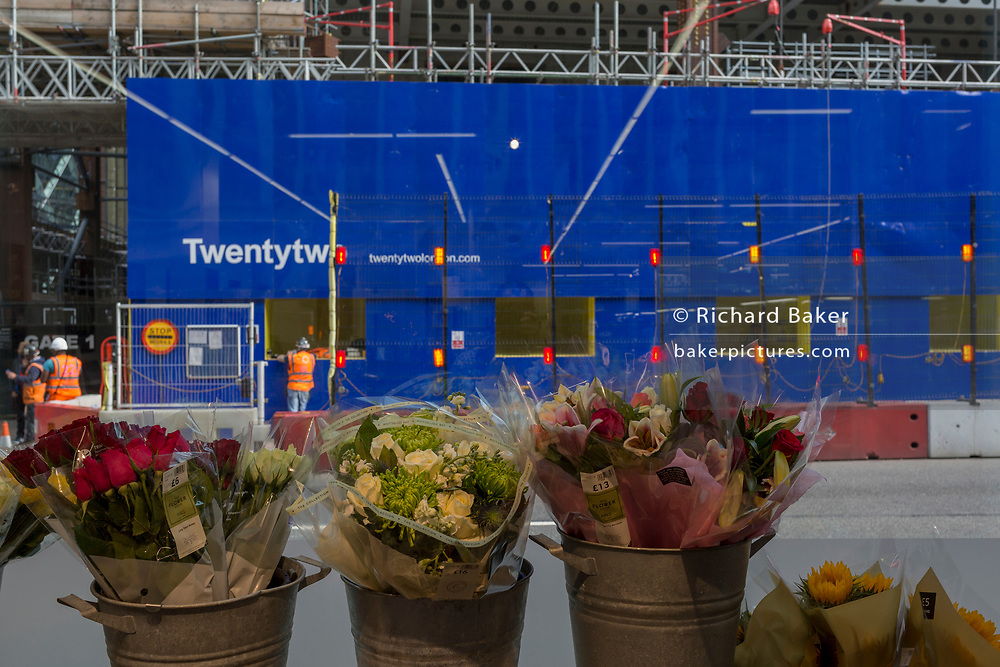 Buckets of fresh flowers and the construction site of 22 Bishopsgate in the City of London - the capital's financial district, on 3rd September 2018, in London England.