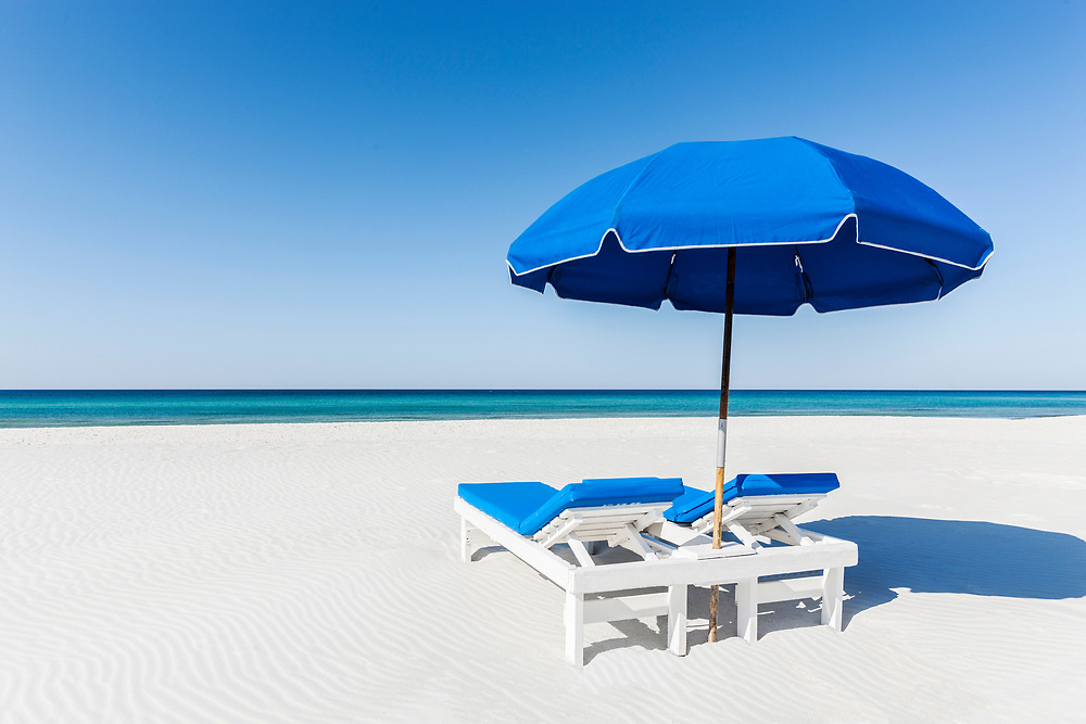 A relaxing beach scene with lounge chairs and umbrella