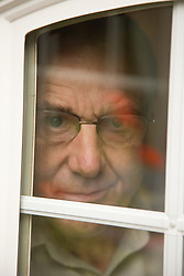 Portrait of an older man looking out of the window,