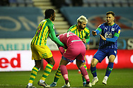 West Bromwich Albion forward Charlie Austin (15) and Wigan Athletic goalkeeper Jamie Jones (23) wrestle for the ball after West Bromwich Albion are awarded the free kick  during the EFL Sky Bet Championship match between Wigan Athletic and West Bromwich Albion at the DW Stadium, Wigan, England on 11 December 2019.
