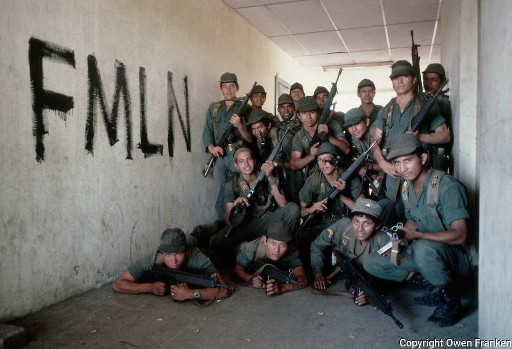 February 1983, El Salvador --- A group of El Salvadoran soldiers poses beside graffiti of their political group, the FMLN. --- Image by © Owen Franken/CORBIS