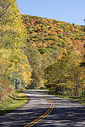 On the Blue Ridge Parkway, view brilliant fall colors in mid October, in North Carolina, USA. This photo is at Blue Ridge Parkway Milepost 455 in the Plott Balsam Range, within the Qualla Boundary between Soco Creek and Soco Gap. The Qualla Boundary is a land trust supervised by the United States Bureau of Indian Affairs for the Tribe of the Eastern Band of the Cherokee Indians, who reside on the adjacent Reservation in western North Carolina. The 469-mile Blue Ridge Parkway was built 1935-1987 to aesthetically connect Shenandoah National Park (in Virginia) with Great Smoky Mountains National Park in North Carolina. The Smokies are a subrange of the Blue Ridge Mountains, part of the Appalachian Mountains.