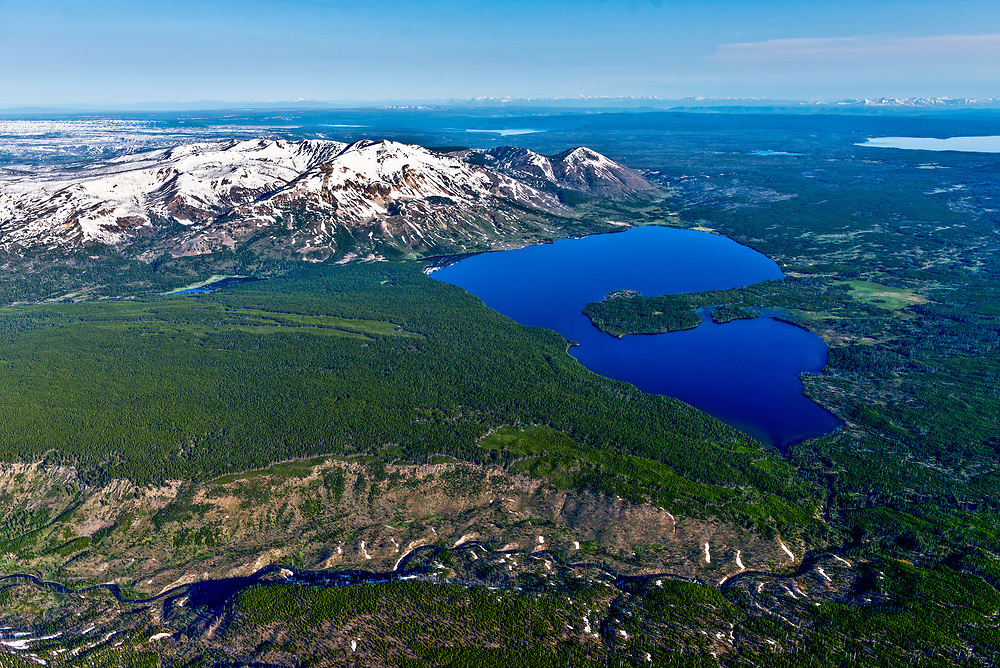 Aerial view of Heart Lake and the headwaters of the Snake River in Yellowstone National Park in springtime with many littel streams combining in high elevations and Yellostone Lake on the distant right horizon