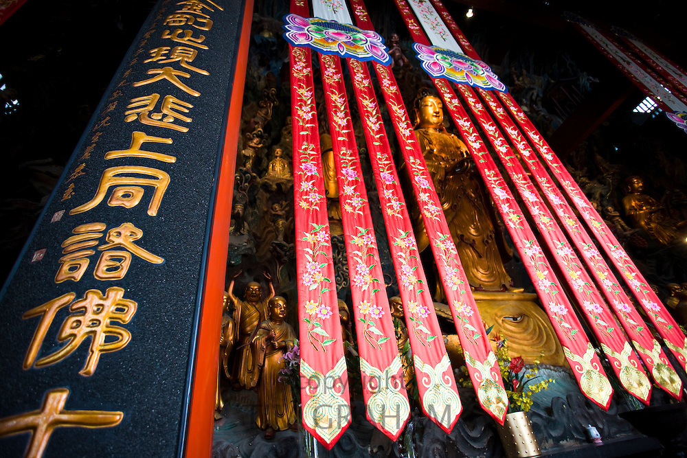 Golden Buddha and silk banners in the Grand Hall of Magnificence of the Jade Buddha Temple, Shanghai, China