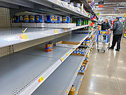 """15 MARCH 2020 - ANKENY, IOWA: A couple shops in the canned goods aisle at the Walmart store in Ankeny. Iowans started hoarding paper products and canned goods over the weekend as fears of coronavirus caused shortages spread. The Governor of Iowa announced Saturday night that the Coronavirus in Iowa had entered the """"community spread"""" phase when a person in Dallas County, in the Des Moines metropolitan area, tested positive for Coronavirus. As of Sunday morning, Iowa was reporting 18 people tested positive for Coronavirus.                     PHOTO BY JACK KURTZ"""