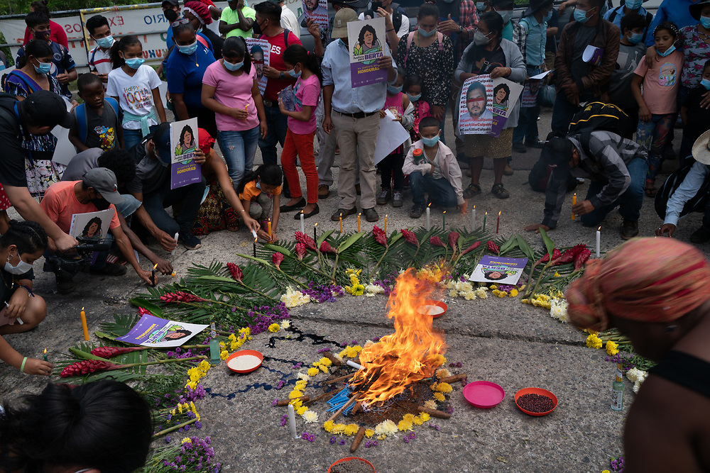 As the result of the trial of David Cáceres is awaited at the Supreme Justice Court, for his part in the assassination of Lenca leader Berta Cáceres, Lenca and Garifuna offerings are made in the street. People carry posters that say Justicia para Berta - Justice for Berta and light candles as incense, candles and tobacco burn.