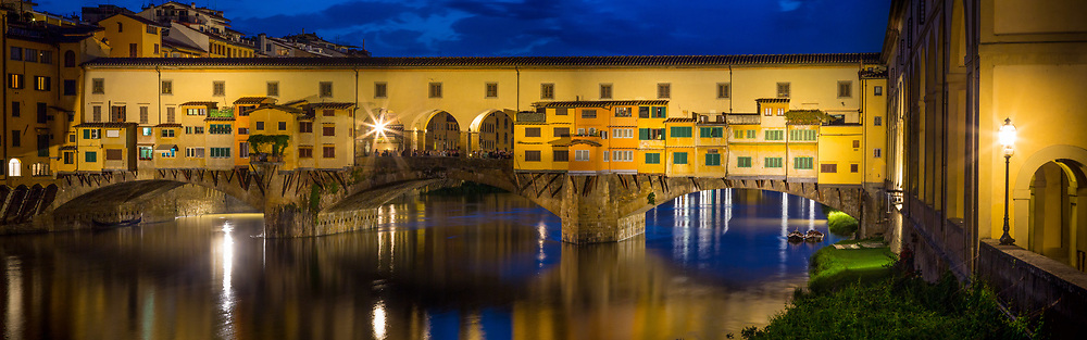 """The river Arno and Ponte Vecchio bridge in Firenze (Florence), Italy.<br /> -----<br /> Captured with a Canon 5D Mk III camera and Canon EF 24-105/4L IS lens  <br /> -----<br /> Florence (Italian: Firenze) is the capital city of the Italian region of Tuscany and of the province of Florence. The Ponte Vecchio (""""Old Bridge"""") is a Medieval stone closed-spandrel segmental arch bridge over the Arno River, in Florence, Italy, noted for still having shops built along it, as was once common. Butchers initially occupied the shops; the present tenants are jewellers, art dealers and souvenir sellers. The Ponte Vecchio's two neighbouring bridges are the Ponte Santa Trinita and the Ponte alle Grazie. The bridge spans the Arno at its narrowest point where it is believed that a bridge was first built in Roman times, when the via Cassia crossed the river at this point. The Roman piers were of stone, the superstructure of wood. The bridge first appears in a document of 996. After being destroyed by a flood in 1117 it was reconstructed in stone but swept away again in 1333 save two of its central piers, as noted by Giovanni Villani in his Nuova Cronica. It was rebuilt in 1345, Giorgio Vasari recorded the tradition in his day, that attributed its design to Taddeo Gaddi, besides Giotto one of the few artistic names of the trecento still recalled two hundred years later. Modern historians present Neri di Fioravanti as a possible candidate. Sheltered in a little loggia at the central opening of the bridge is a weathered dedication stone, which once read Nel trentatrè dopo il mille-trecento, il ponte cadde, per diluvio dell' acque: poi dieci anni, come al Comun piacque, rifatto fu con questo adornamento. The Torre dei Mannelli was built at the southeast corner of the bridge to defend it.<br /> The bridge consists of three segmental arches: the main arch has a span of 30 meters (98 ft) the two side arches each span 27 meters (88 ft). The rise of the arches is between 3.5 and 4.4 meters (11"""