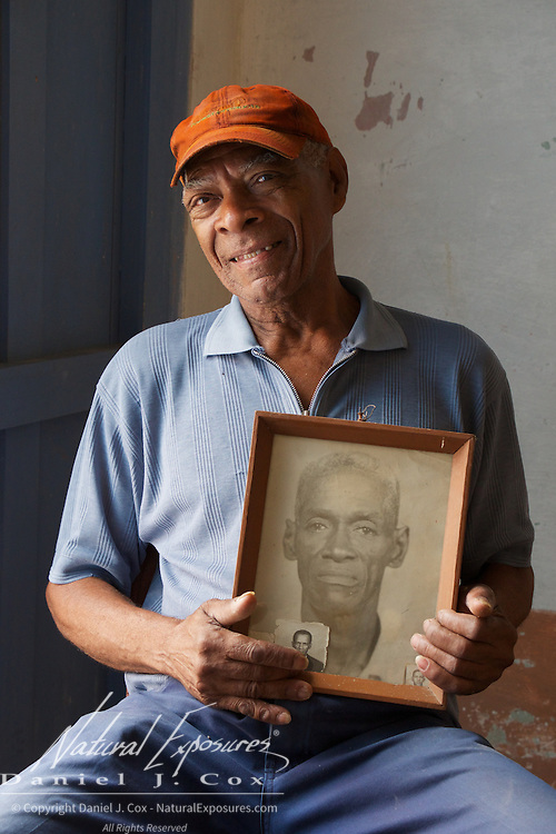 An older gentleman holds a photograph of his father at his home in Trinidad, Cuba.