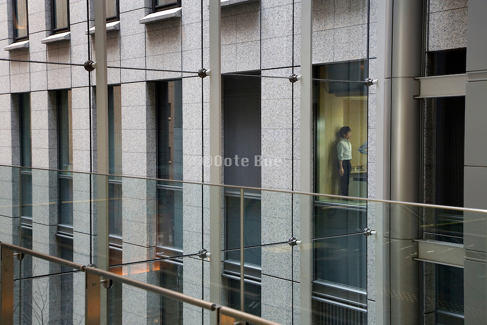businessman standing against wall after regular office hours, Tokyo Japan