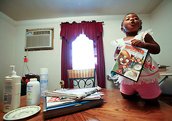 09 July 2006. New Orleans. Louisiana. <br /> Finding Faith. <br /> Faith Figueroa. A day in the life of. Faith climbs onto a table with a DVD on a rainy Sunday afternoon.<br /> Following a ten month search for the little girl whose face appeared on the Sept 19th, 2005 cover of Newsweek magazine, Faith's mother, Miriam Figueroa has returned to town with her three children. Faith, (1 yrs), Anfernya (5yrs) and Jacquelyn (13 yrs). <br /> Credit; Charlie Varley/varleypix.com