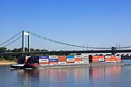 container vessel on the river Rhine, the Muelheimer bridge, Cologne, Germany.<br /> <br /> Containerschiff auf dem Rhein, Muelheimer Bruecke, Koeln, Deutschland.