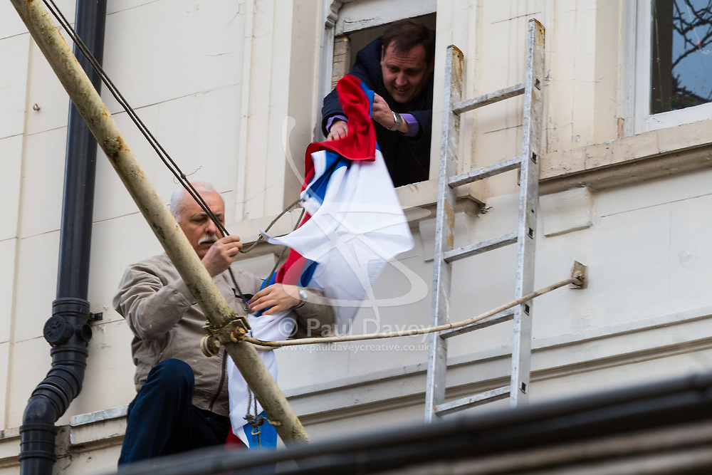 Workers remove the Russian flag at the Russian embassy in Kensington, replacing it with a new one, on the day of British Prime Minister Theresa May's decision to expel 23 diplomatic officials in the wake of the Salisbury poisoning incident which has former double agent Sergei Skripal and his daughter along with a police officer who tried to assist.. London, March 14 2018.