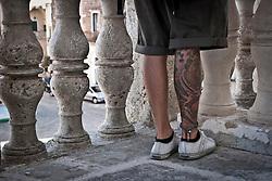 """Siamo in Puglia, a Specchia cittadina della provincia di Lecce, situato a circa 60 Km a sud del capoluogo di provincia..Si presenta come un paese tranquillo ma vivo..Le strade luminose e pulite presentano una pavimentazione a lastroni antichi..Il centro storico è un'area pedonale ed è spesso scenario di manifestazioni sacre e culturali..La gente è gentile ed ospitale e si è lasciata fotografare con tranquillità, facendosi riprendere nel loro fare quotidiano, quasi fosse abituata ad essere fotografata..Quest'area del Salento è meta di un turismo alla ricerca della tranquillità e della cultura; cultura intesa anche come eno-gastronomia, e soprattutto cultura volta al rispetto della natura..I turisti in cerca di aria sana, pulita, vengono nei paesini dell'entroterra salentino, lontani dalla città e dallo smog..Appena entrati in paese ci si ritrova una piazzetta moderna, molto ben concepita architettonicamente, sulla quale si affacciano anche palazzi di età più antica, probabilmente dell'inizio del '900...La Piazza del popolo, al momento degli scatti si preparava ad ospitare la """" Notte Bianca di Specchia""""..Il campanile si affaccia sulla piazza e sulle viuzze vicine e con i suoi rintocchi fa rivivere riti e abitudini ormai abbandonati..Architettonicamente il campanile si compone di tre ordini e nel primo ha l'orologio che ancora oggi scandisce il tempo di Specchia..Di fronte al campanile vi è il Palazzo Risolo, oggi il palazzo è il risultato di vari rimaneggiamenti e cambiamenti anche strutturali apportati nel corso del tempo a partite dal XV secolo..Una balaustra, che divide in due fasce orizzontali la facciata, si affaccia sulla piazza offrendo una visuale suggestiva della architettura urbana del centro storico."""