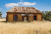 dilapidated old sandstone farm house in a field of long dry grass near Palmer, South Australia, Australia <br />