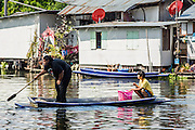 03 JANUARY 2013 - BANGKOK, THAILAND: Boys in a small boat in Phra Khanong canal near Wat Mahabut. Just a few minutes from downtown Bangkok, the neighborhoods around Wat Mahabut interlaced with canals, still resemble the Bangkok of 60 years ago. Wat Mahabut is a large temple off Sukhumvit Soi 77. The temple is the site of many shrines to Thai ghosts. Many fortune tellers also work on the temple's grounds.   PHOTO BY JACK KURTZ