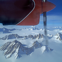 ANTARCTICA, TRANS-ANTARCTIC MOUNTAINS. Ski-equipped Twin Otter owned by the pioneering Antarctic aviation company, Adventure Network, flies over Gothic Mountains, a sub-range of the Queen Maud Mountains, at 86 degrees south latitude. The Organ Pipes are the prominent spires in center.