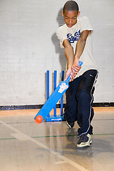 Boy playing a game of indoor cricket in the sports hall of his local leisure centre,