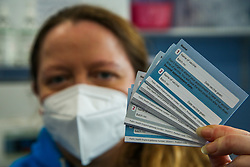 © Licensed to London News Pictures. 14/04/2021. London, UK. A NHS staff holds vaccination record cards at a vaccination centre in Haringey, north London. In the UK, over 32 million people have received a first dose. People aged 45 to 49 are now invited to book their appointments as part of the next phase of the government's vaccination programme. <br /> <br /> ***Permission Granted*** <br /> <br /> Photo credit: Dinendra Haria/LNP