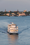 Sunset tour boat Spirit of Carolina crosses the Ashley River with the city skyline behind at sunset in Charleston, South Carolina.