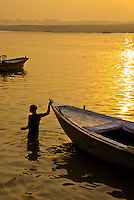 A Boatman takes a morning Bath in the River Ganges in Varanasi, Uttar Pradesh, India