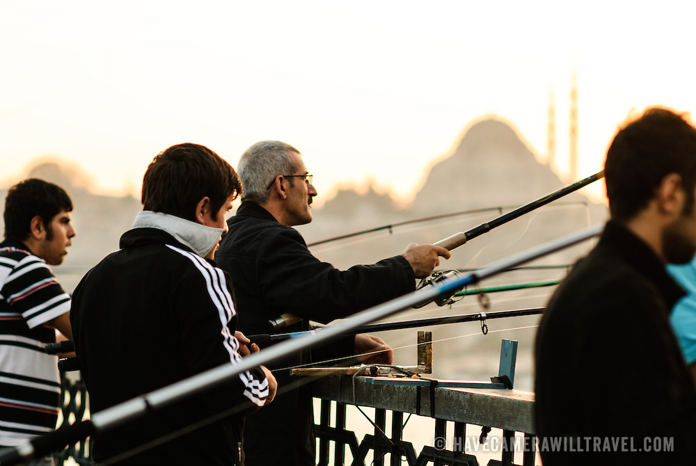 Fishing off Istanbul's historic Galata Bridge spanning the Golden Horn with the silhouette of one of the city's several impressive mosques in the background skyline.