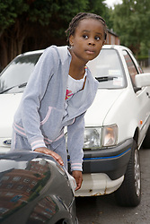 Girl trying to cross a road; looking out from between two vehicles,