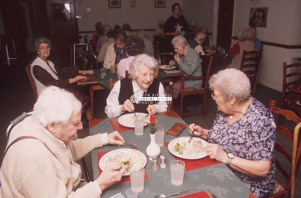 Group of elderly people eating meal at day centre,