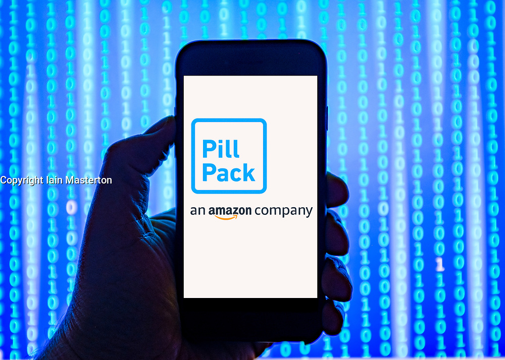 Person holding smart phone with  amazon Pill-Pack online pharmacy website  logo displayed on the screen. EDITORIAL USE ONLY
