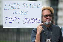 A man holds a sign referring to donations to the Conservative Party from property developers at a protest opposite Downing Street by leaseholders and tenants living in unsafe homes on 15th July 2021 in London, United Kingdom. Some leaseholders are faced with crippling costs to fix safety issues and they called on the government to ensure that their homes are made safe from fire as a matter of priority, to make interim payments and to cover fire safety remediation costs and to find a solution with mortgage lenders which enables them to move on with their lives.
