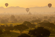 Three hot air balloons at sunrise drift over the vast plain of temple ruins in Bagan, Myanmar