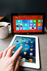 Man using Microsoft Surface rt tablet computer and iPad 3 in cafe