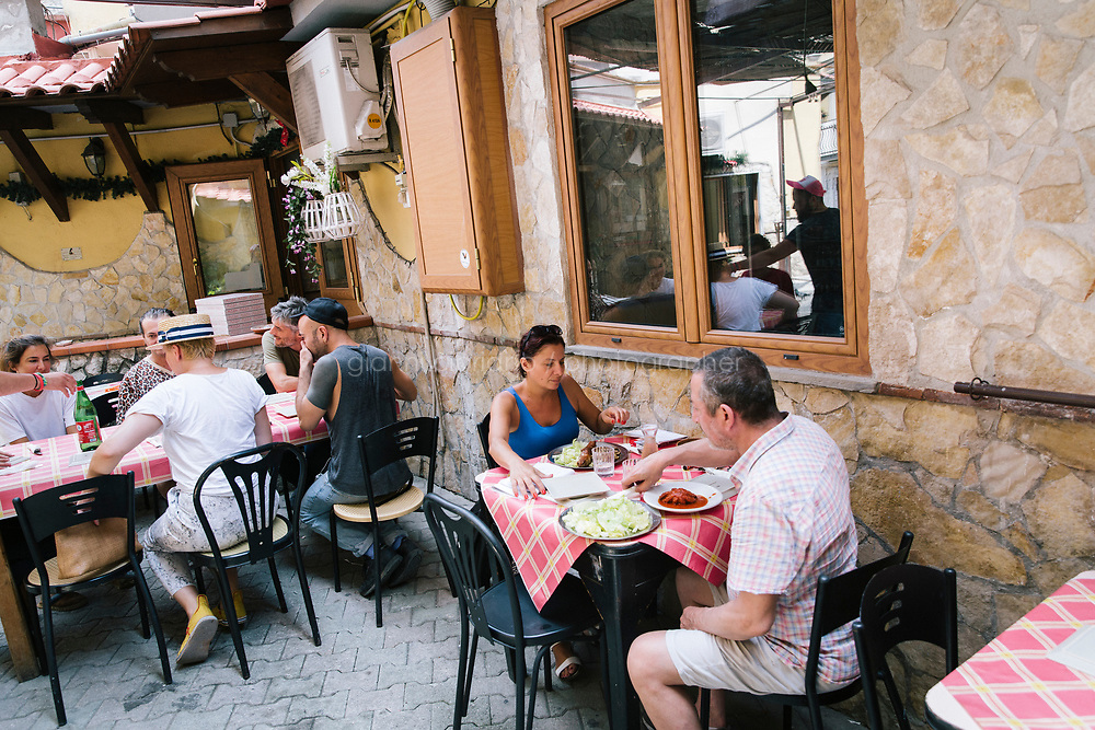 NAPLES, ITALY - 1 AUGUST 2018: Customers have lunch at Cantina del Gallo, a family-owned restaurant in the Rione Sanità in Naples, Italy, on August 1st 2018.<br /> <br /> Cantina del Gallo, in the Rione Sanità, was established in 1898 and run by four generations of the Silvestri family. The cantina began as a store selling bulk wine and oil. It was only in the 1950s, when the legendary Aunt Cuncetta began cooking, that it became the simple and genuine tavern it is today.<br /> There are three dishes that are the restaurant's workhorses, and the ones we always seem to rotate between: the pennette alla sorrentina (a variation of the classic gnocchi alla sorrentina, seasoned with tomato, basil and stringy mozzarella), the baked cod (although the fried cod is just as mouth-watering) and the pizza cafona (peasant pizza), topped with oregano, cheese, chile and with double the tomatoes (tomato juice and chopped tomatoes).