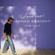 """VENICE, ITALY - MAY 31:  A man walks in front of the panel dedicated to  """"Ahmed Basiony"""" who was killed during the Tarhir Square events, outside the Egypt Pavillion at the Giardini Biennale on May 31, 2011 in Venice, Italy. This year's Biennale, the 54th edition, will  officially open  on Saturday June 4th, after several days of press previews, and will run until 27 November  (Photo by Marco Secchi/Getty Images)"""