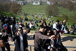 © Licensed to London News Pictures. 04/04/2021. London, UK. Members of the public take selfies as others relax and enjoy the sunny weather in Greenwich Park in South East London. Temperatures are expected to rise with highs of 16 degrees forecasted for parts of London and South East England today . Photo credit: George Cracknell Wright/LNP