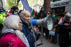 London, UK. 11th May, 2021. Eric Levy, 92, addresses activists from Palestine Action at a protest outside the UK headquarters of Elbit Systems, an Israel-based company developing technologies used for military applications including drones, precision guidance, surveillance and intruder-detection systems. The activists were protesting against the company's presence in the UK and in solidarity with the Palestinian people following attempts at forced evictions of Palestinian families in the Sheikh Jarrah neighbourhood of East Jerusalem, the deployment of Israeli forces against worshippers at the Al-Aqsa mosque during Ramadan and air strikes on Gaza which have killed several children.