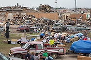 May 25, 2013, Volunteers handle donated supplies dropped off in front of a  makeshift memorial made of stuffed animals attached to a fence around what remains of the Twin Tower Plaza Elementary school in Moore Oklahoma. Seven children died inside the school after the EF5 tornado struck. The school did not have a storm shelter.