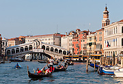 """Gondoliers row gondolas on the Grand Canal at Rialto Bridge (or Ponte di Rialto, built 1591), which is the oldest of four bridges spanning the Grand Canal in Venice, Italy, Europe. The single span stone bridge designed by Antonio da Pontestone is an architectural icon of Venice. In 452 AD, Attila the Hun invaded Italy, and people retreated to offshore islands called Rivo Alto (high bank), or Ri'Alto, the center of Venice. Venice/Venezia is the capital of Italy's Veneto region, named for the ancient Veneti people from the 900s BC. The romantic """"City of Canals"""" stretches across 100+ small islands in the marshy Venetian Lagoon along the Adriatic Sea in northeast Italy. The Republic of Venice was a major maritime power during the Middle Ages and Renaissance, a staging area for the Crusades, and a major center of art and commerce (silk, grain and spice trade) from the 1200s to 1600s. The wealthy legacy of Venice stands today in a rich architecture combining Gothic, Byzantine, and Arab styles. Venice and the Venetian Lagoons are on the prestigious UNESCO World Heritage List."""