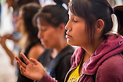 "12 JULY 2012 - FT DEFIANCE, AZ: Navajo teenagers pray during the youth worship at the 23rd annual Navajo Nation Camp Meeting in Ft. Defiance, north of Window Rock, AZ, on the Navajo reservation. Preachers from across the Navajo Nation, and the western US, come to Navajo Nation Camp Meeting to preach an evangelical form of Christianity. Evangelical Christians make up a growing part of the reservation - there are now more than a hundred camp meetings and tent revivals on the reservation every year. The camp meeting in Ft. Defiance draws nearly 200 people each night of its six day run. Many of the attendees convert to evangelical Christianity from traditional Navajo beliefs, Catholicism or Mormonism. ""Camp meetings"" are a form of Protestant Christian religious services originating in Britain and once common in rural parts of the United States. People would travel a great distance to a particular site to camp out, listen to itinerant preachers, and pray. This suited the rural life, before cars and highways were common, because rural areas often lacked traditional churches.      PHOTO BY JACK KURTZ"