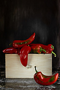 Red sweet cayenne peppers inside wooden drawer.