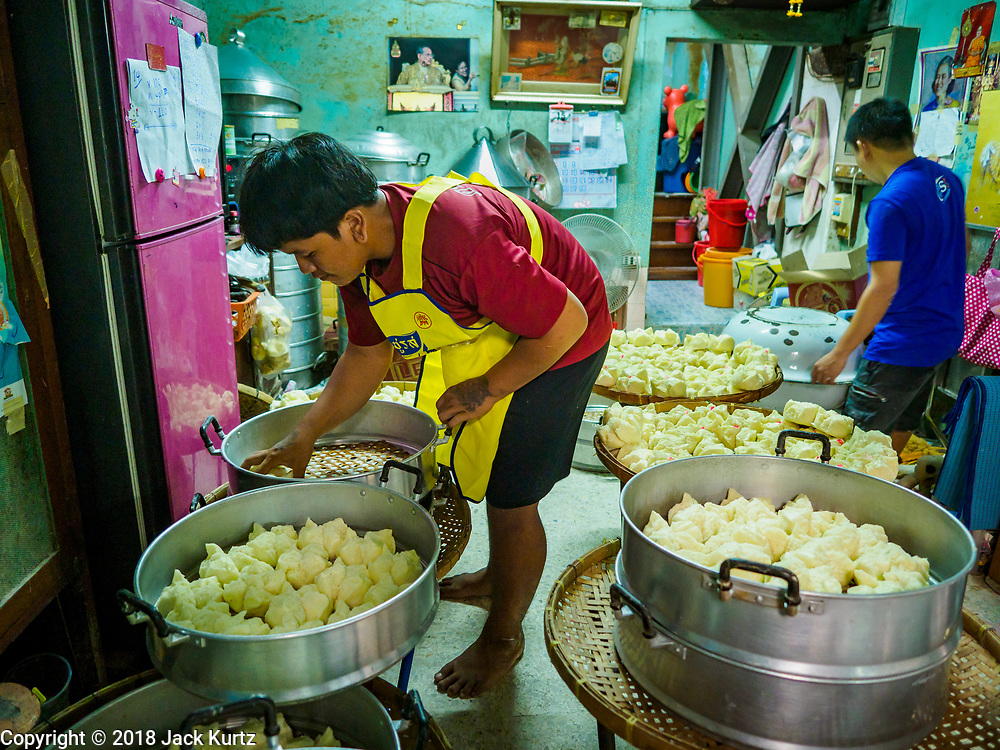 """12 FEBRUARY 2018 - BANGKOK, THAILAND:  Men set out freshly steamed buns in a home that makes steamed Chinese buns, called """"bao"""" in the Chinatown neighborhood of Bangkok. Bao are eaten at midnight on the Lunar New Year and served to guests during New Year's entertaining. Lunar New Year, also called Tet or Chinese New Year, is 16 February this year. The coming year will be the Year of the Dog. Thailand has a large Chinese community and Lunar New Year is widely celebrated in Thailand, especially in Bangkok and large cities with significant Chinese communities.   PHOTO BY JACK KURTZ"""