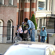 NLD/Amsterdam/20070405 - Partner Thomas Acda met kinderen op de fiets voor hun woning