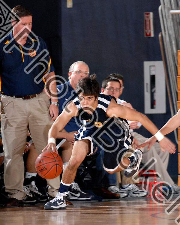 2011 January 15 - Coach Jose Roca watches as Belen Jesuit Wolverines guard Manuel Sicre (5) drives into an offensive play. Belen Jesuit Wolverines varsity basketball team falls to the Columbus Explorers 52-75 at U.S. Century Bank, Miami, Florida.
