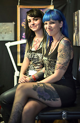 © licensed to London News Pictures. 26/09/2014<br /> The 10th London International Tattoo Convention, one of the most prestigious body art conventions in the world, brought together 400 of the best tattoo artists to thousands of admirers at Tobacco Dock. Other attractions and alternative performances included burlesque, sword swallowing, striptease dancers, fire-dancers and trapeze performers. Pictured. Tattoo artists working at the today's convention.<br /> Photo credit : Ian Whittaker/LNP