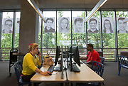 """portraits of Skyview students are displayed in the windows of the Vancouver Library as people use computers Thursday May 17, 2018. Skyview photography students created the public art project called  """"Inside Out""""  The portraits will dominate the streetscape outside the library for a month. (Photo by Natalie Behring for the Columbian)"""