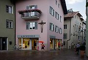 Woman carrying red umbrella walks towartds shop, under large town crucifix in Klausen-Chiusa in the Italian south Tyrol. Using an umbrella against the summer shower, she walks towards the town centre beneath a large cross. Klausen (Italian: Chiusa) is a commune (municipality) in South Tyrol in northern Italy, located about 20 kilometres (12 mi) northeast of the city of Bolzano. In the 2011 census, 91.3% of the population speak German, 7.9% Italian and 0.8% spoke the ancient Ladin langauge as their mother tongue. South Tyroleans are almost all Catholics and quite conservative - though it depends on the areas and they erect such shrines almost anywhere though especially in vineyards or meadows or in villages where an agricultural holy omen is welcomed for good harvests.