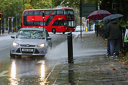 © Licensed to London News Pictures. 04/10/2020. London, UK. Members of the public try to avoid splashing rainwater as a car drives through surface water in north London, as Storm Alex brings heavy rain to large parts of the UK. The Met Office forecasts heavy rain and windy weather for the next of the day in the capital. Photo credit: Dinendra Haria/LNP
