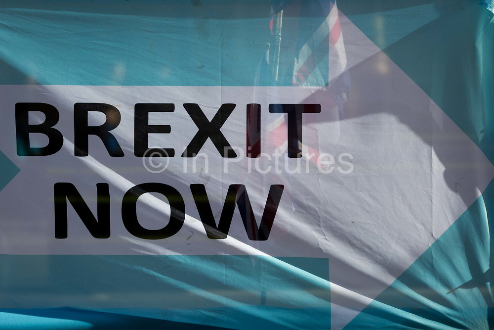 On the day that the EU in Brussels agreed in principle to extend Brexit until 31st January 2020 aka Flextension and not 31st October 2019, a Union Jack flag is seen through a Brexit Party flags and banners during a Brexit protest outside parliament, on 28th October 2019, in Westminster, London, England.